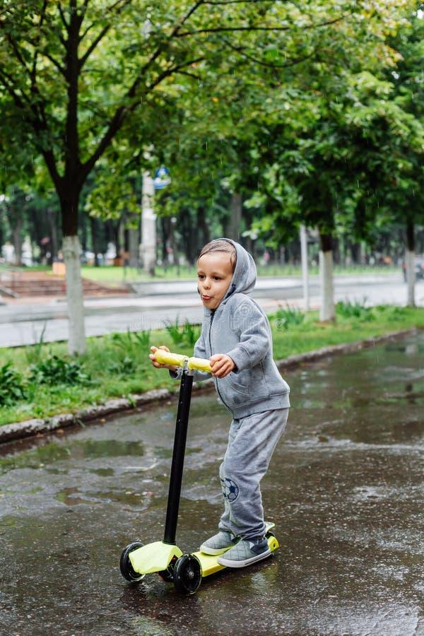 Doorweekt in de regen, schaatst een jongen in een sportkostuum op een autoped De lentegang in het stadspark, regenachtig weer royalty-vrije stock foto