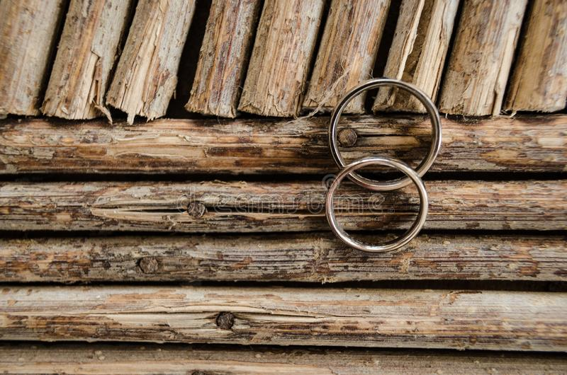 Doorweven en overladen trouwringen op een patroon met stokken van natuurlijk die hout, patroon van lijnen van natuurlijke houten  royalty-vrije stock afbeelding