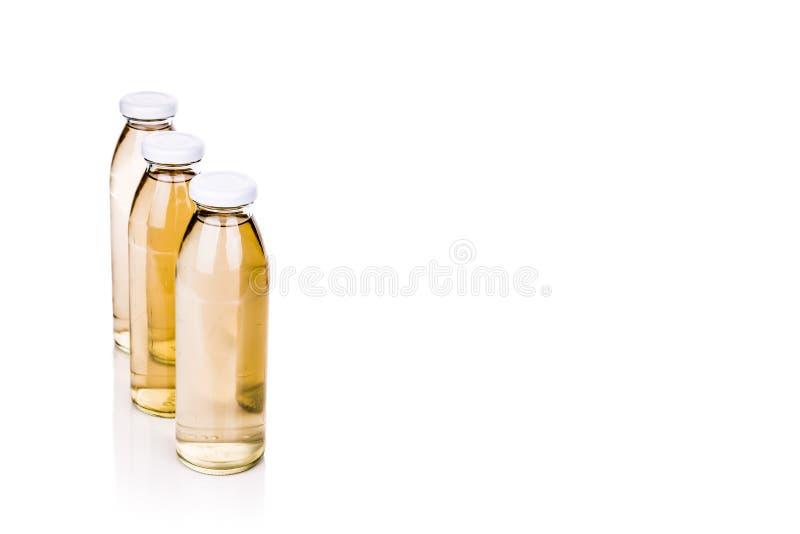Doorzichtige vloeistof drie in glasfles op witte achtergrond stock foto's