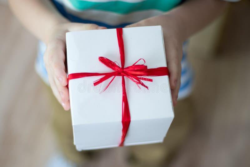 Doos met een gift in de handen van een kind stock afbeelding