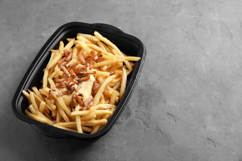 Doos met Frieten, bacon en kaas stock afbeelding