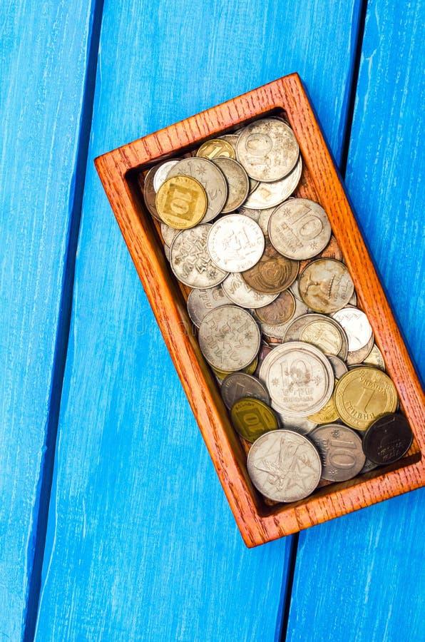 Doos met muntstukken van landen van de wereld op een blauwe houten backgr royalty-vrije stock afbeelding