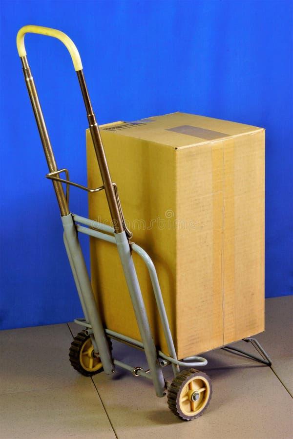 Doos op een kar, levering van goederen en pakketten De doos of de kartondoos worden op een hand vervoerd die kar vouwen - het bes stock afbeeldingen