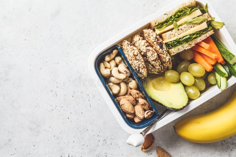 Doos van de school de gezonde lunch met sandwich, koekjes, vruchten en avocado op witte achtergrond royalty-vrije stock foto's