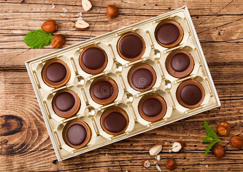 Doos van eigengemaakt suikergoed op houten achtergrond met munt en noten Een hazelnoot in Karamel en chocolade stock fotografie