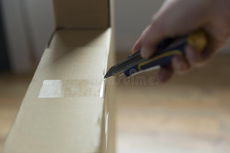 Doos van het vrouwen de unboxing karton nieuw meubilair met mes stock foto's