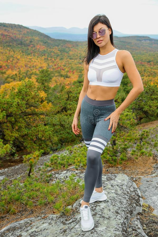Dopasuj brunetki na szczycie skalistej góry obrazy stock