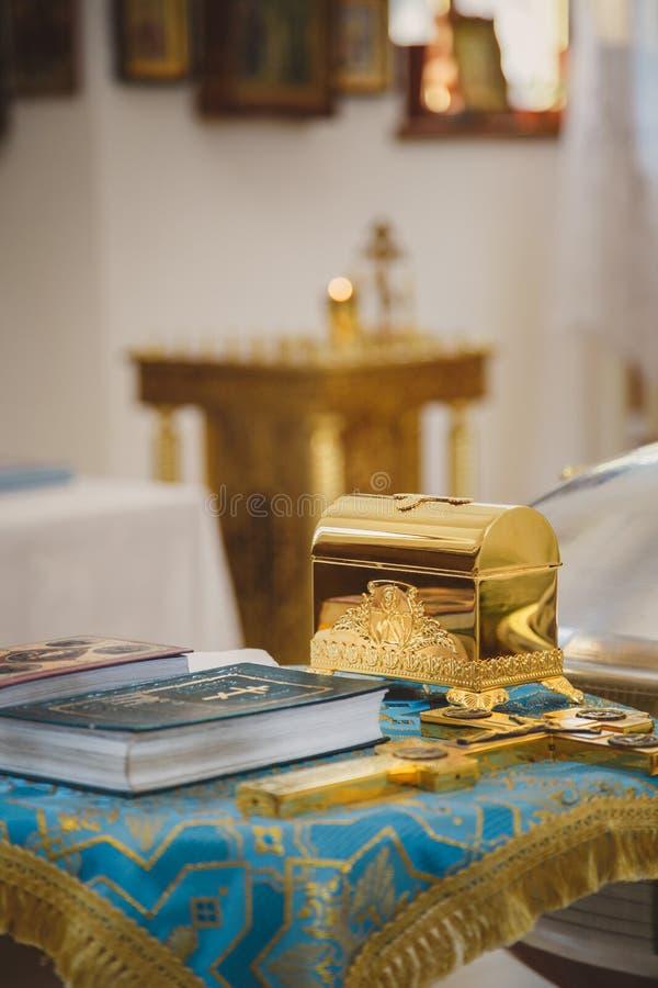 Dopend in de kerk, gouden godsdienstige werktuigen: bijbel, kruis, gebedboek, missaal Details in Orthodox Christian Church royalty-vrije stock foto