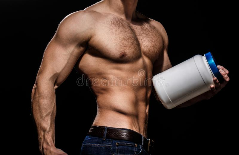 Doping, anabolic, protein, steroid, sport vitamin, bodybuilder and bodybuilding. Muscles strong, muscular. Dieting. Fitness. Man with muscular body hold pill royalty free stock images