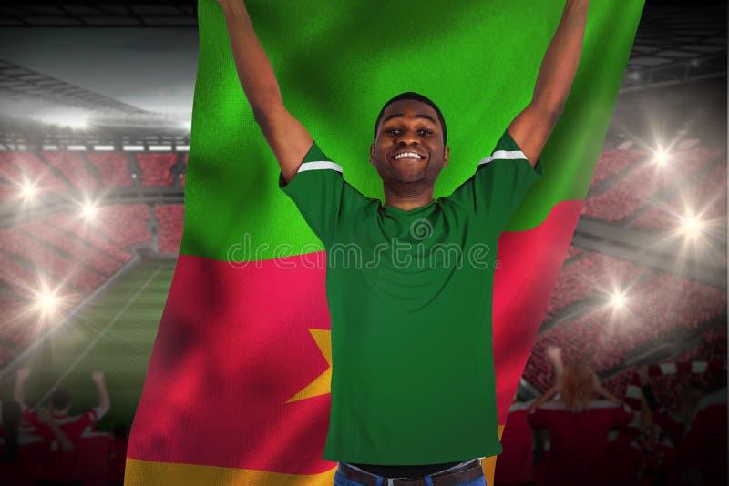 Dopingu fan piłki nożnej w zielonej dżersejowej trzyma Cameroon flaga obraz royalty free