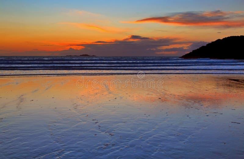 Dopo il tramonto l'incandescenza bruno fulva ha riflesso in sabbia bagnata immagini stock libere da diritti