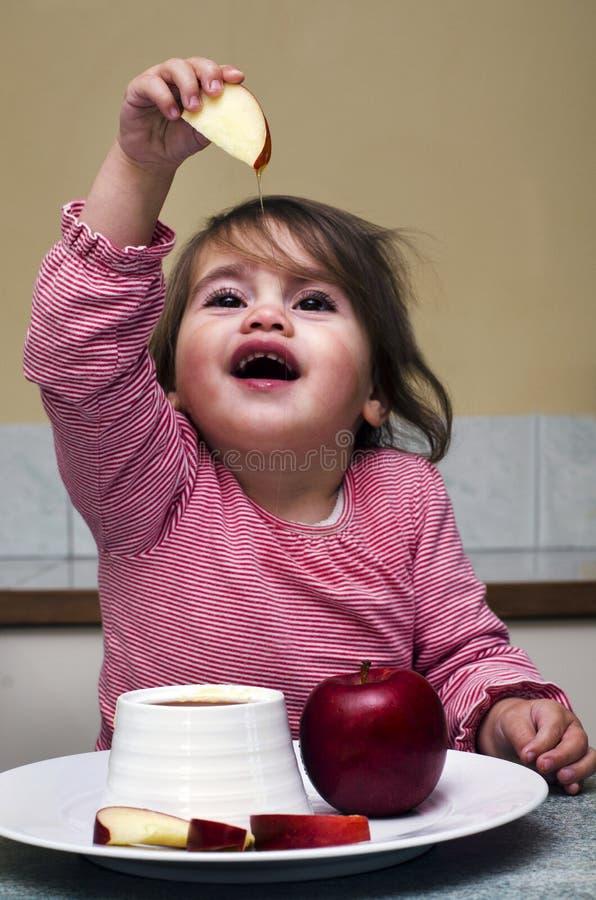 Doppa äppleskivor för liten judisk flicka in i honung arkivfoto
