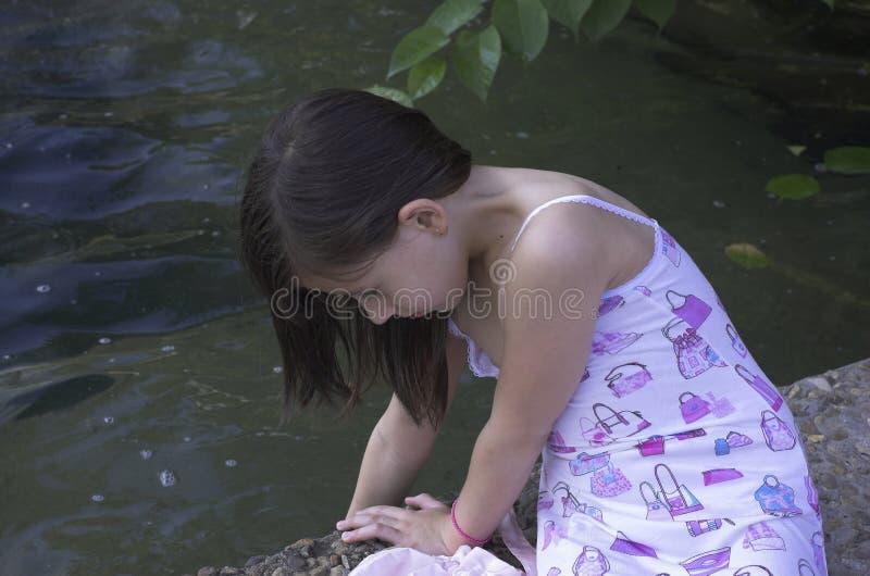 Doppa hand för flicka i damm arkivbild