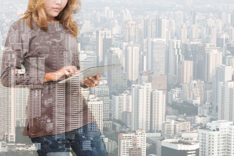 Doppelbelichtung der Frau, die Tablettentechnologie und städtische Gestalt verwendet stockfoto