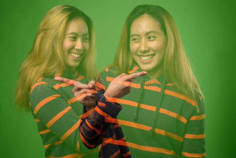 Doppelbelichtung der jungen Asiatin gegen grünen Hintergrund stockfoto