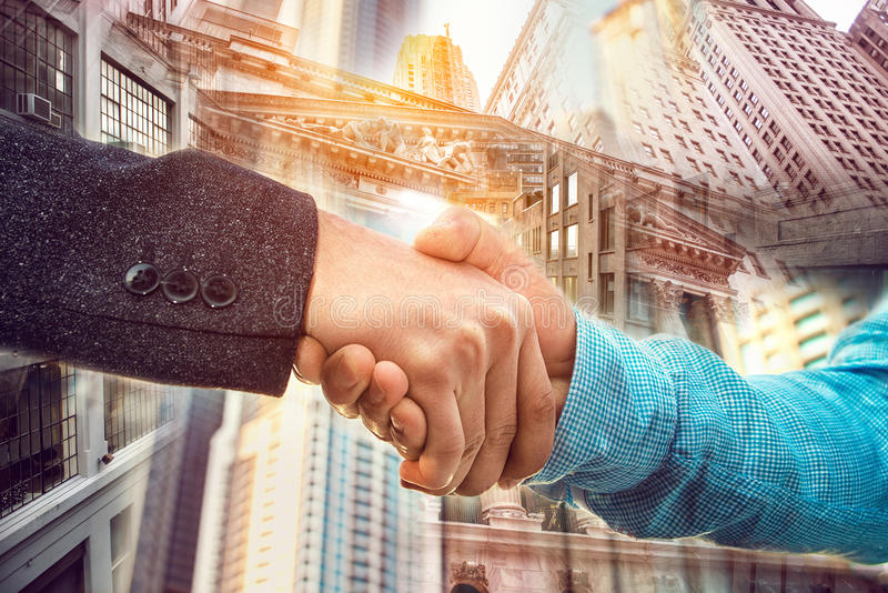 Doppelbelichtung des Geschäftsmannhändedrucks auf Hintergrund New York City Wall Street lizenzfreie stockfotos