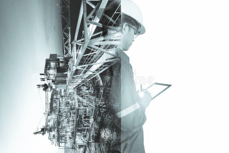 Doppelbelichtung des Ingenieur- oder Technikermannes mit Schutzhelm betriebener Plattform oder Anlage durch die Anwendung der Tab lizenzfreies stockbild