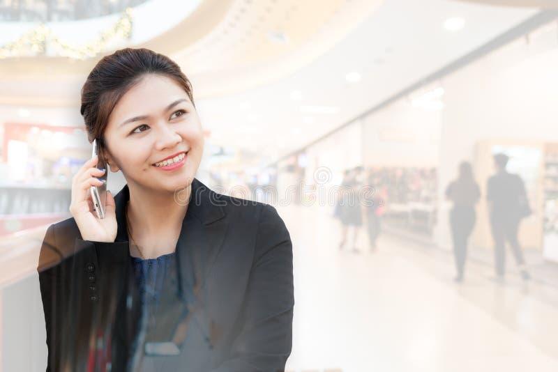 Doppelbelichtung des Unterhaltungstelefons der Geschäftsfrau mit Einkaufszentrum stockfotografie