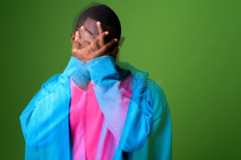 Doppelbelichtung geschossen vom jungen afrikanischen Mann gegen grünen Hintergrund stockfoto