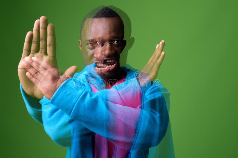 Doppelbelichtung geschossen vom jungen afrikanischen Mann gegen grünen Hintergrund stockbild