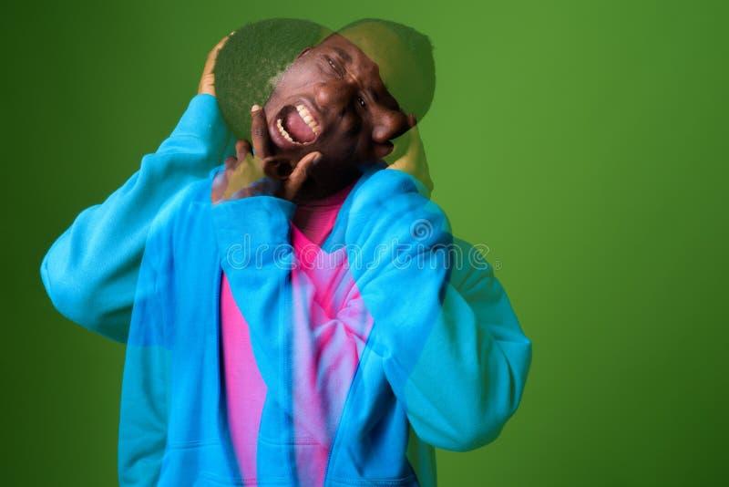 Doppelbelichtung geschossen vom jungen afrikanischen Mann gegen grünen Hintergrund lizenzfreie stockbilder