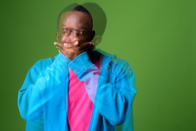 Doppelbelichtung geschossen vom jungen afrikanischen Mann gegen grünen Hintergrund lizenzfreie stockfotos