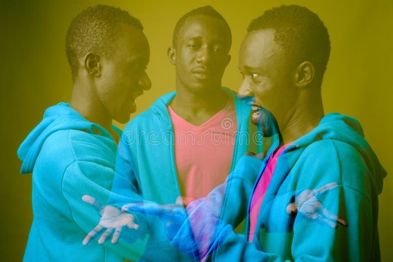 Doppelbelichtung geschossen vom jungen afrikanischen Mann gegen grünen Hintergrund stockfotos
