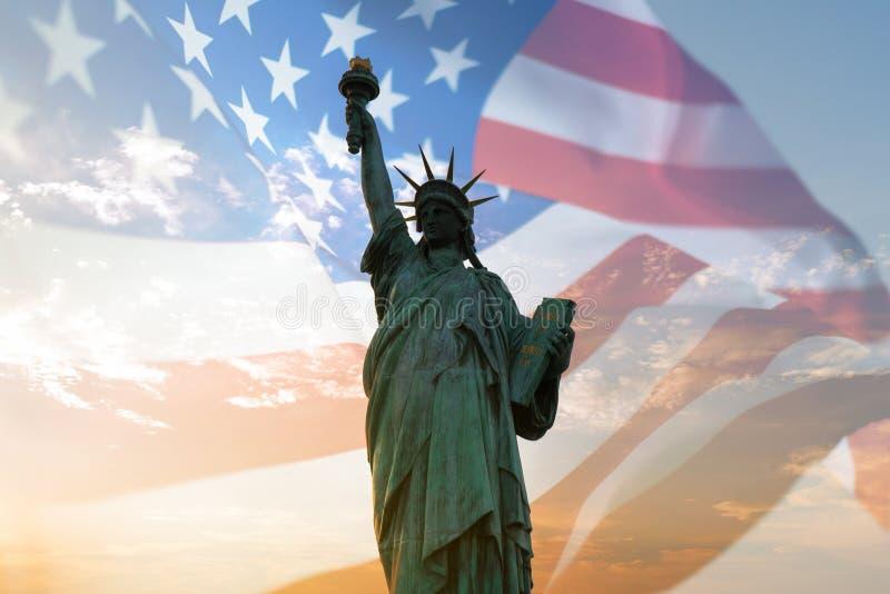 Doppelbelichtung mit Freiheitsstatuen und Flagge Vereinigter Staaten durchbrennend im Wind stockbild