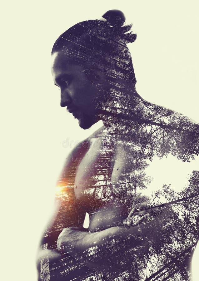 Doppelbelichtung: muskulöser junger Mann- und Kiefernwald stockfoto
