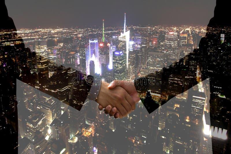 Doppelbelichtungs-Geschäftshanderschütterung mit Stadtlicht nachts lizenzfreie stockfotografie