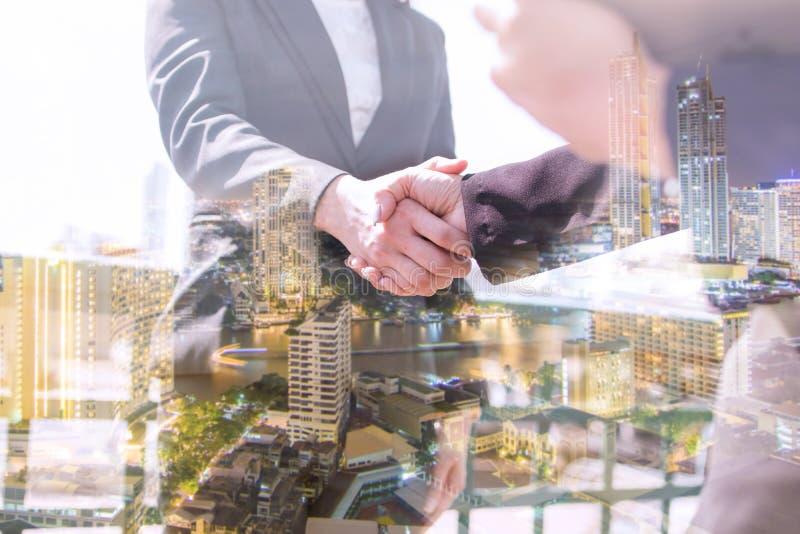 Doppelbelichtungsgeschäftsleute rütteln Hand- und Verhandlungs- und Nachtstadt, erfolgreiches Diskussionskonzept lizenzfreies stockbild