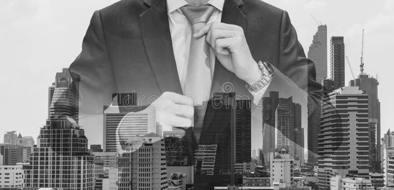 Doppelbelichtungsgeschäftsmann, der Halsbindung mit modernen Gebäuden im Bangkok-Stadthintergrund, Schwarzweiss hält stockfotos