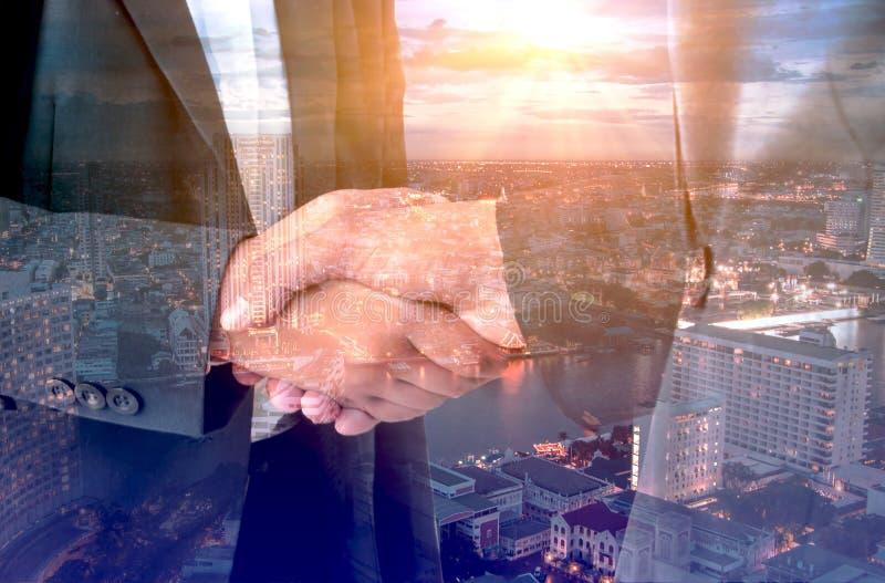 DoppelbelichtungsGeschäftsmann, der Hand für Geschäft wirkliches esta rüttelt stockfoto