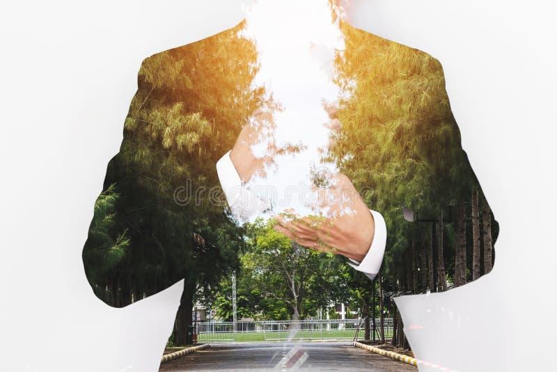 Doppelbelichtungsgeschäftsmann mit dem Fahrweg mit Baumreihe und hellem Licht stockfoto