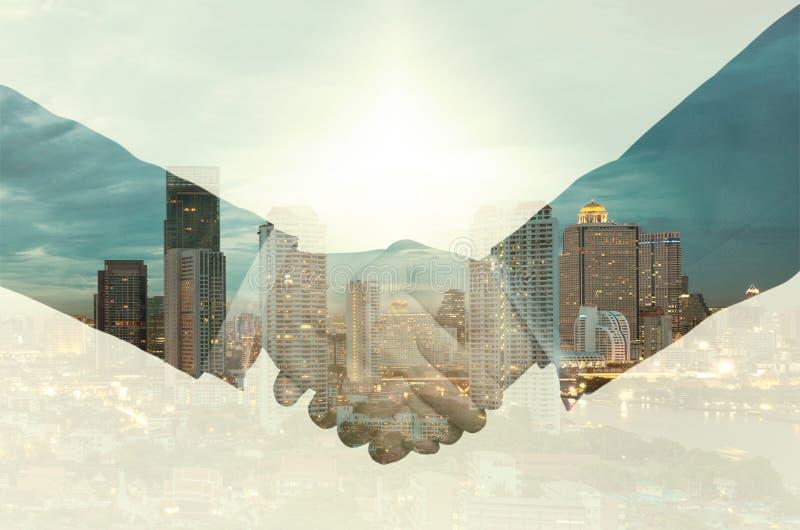 Doppelbelichtungshändedruck zwischen Geschäftsmann auf einem Stadt backgrou stockfotografie