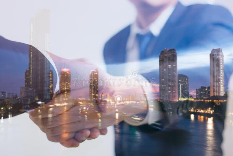 Doppelbelichtungskonzept Investorgeschäftshändedruck mit Stadtnacht Geschäftsmann, der Hände rüttelt lizenzfreies stockbild