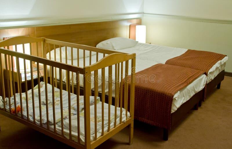 Doppelbettraum mit Babyfeldbett stockfotografie