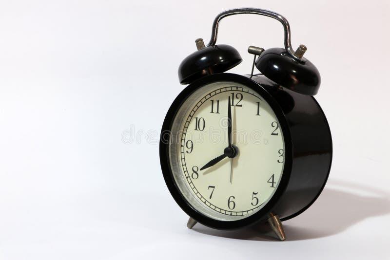 Doppelglockenweckerschwarzfarbe auf acht Uhr gesetzt auf den weißen Boden stockbild