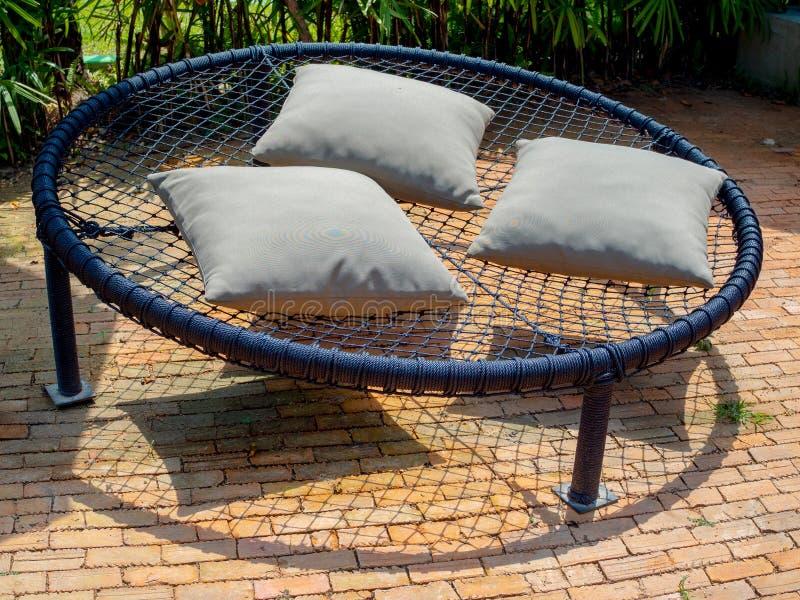 Doppelseile mit drei Kissen im Garten mit schwarzem, rundem Makramsofa stockfoto