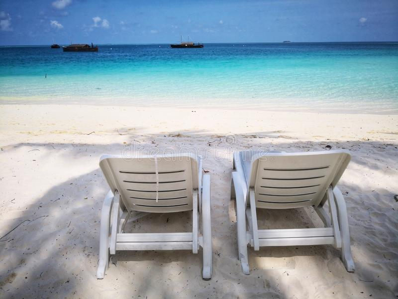 Doppelstrandstühle auf feinem weißem Sand lizenzfreies stockfoto