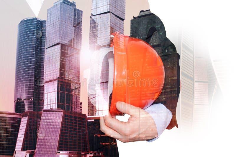 Doppelte Ausstellung eines Fotos des Wolkenkratzerarchitekten mit einem Bausturzhelm Das Konzept des Erfolgs, Geschäft, Architekt lizenzfreie stockfotos