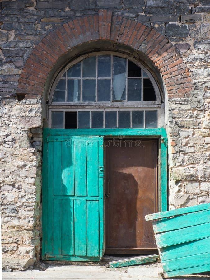 Doppelte grüne Holztür mit defektem Blatt lizenzfreie stockfotografie