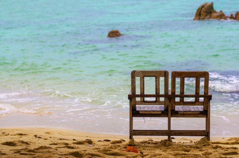 Doppelte Holzstühle, zum in dem Meer auf dem Strand zu sitzen lizenzfreies stockbild