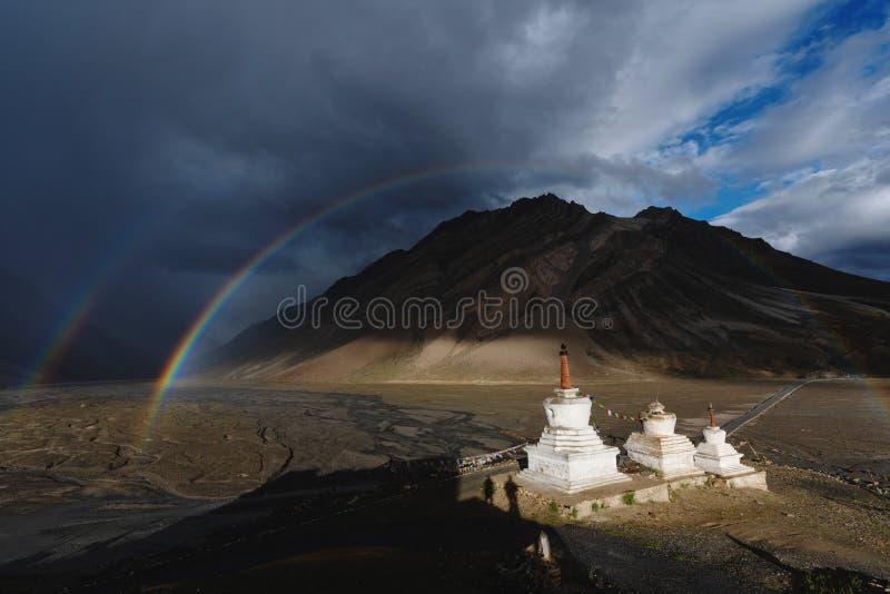 Doppelte Regenbogen und bewölkter regnerischer Himmel und Pagoden in Zanskar-Tal, Indien stockfotografie