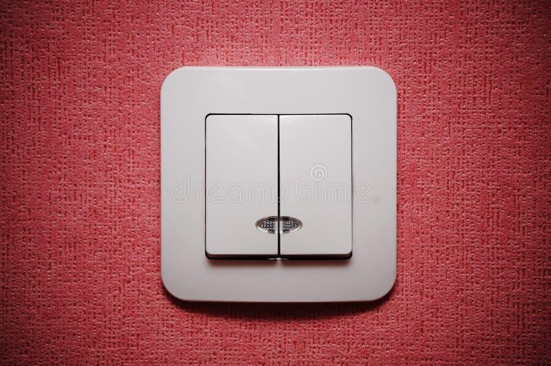 Doppelter heller Schalter gegen rote Wand lizenzfreie stockfotografie