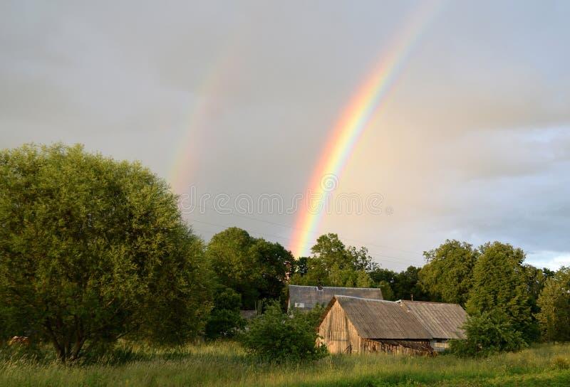 Doppelter Regenbogen über dem Wald und den Häusern an der Landschaft lizenzfreie stockfotografie