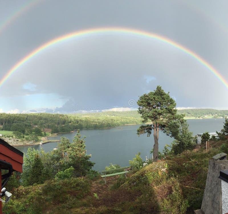 Doppelter Regenbogen über See stockfotos