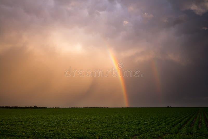 Doppelter Regenbogen u. Sturm-Wolken lizenzfreie stockbilder