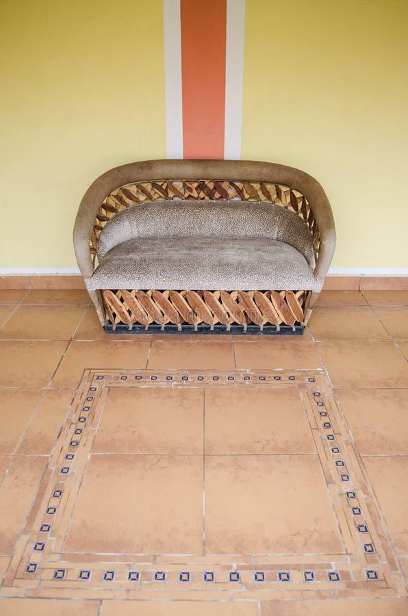 Doppelter Stuhl gemacht vom Holz mit braunen Kissen auf einem Boden von braunen Tönen in einem Korridor eines Hauses lizenzfreies stockbild