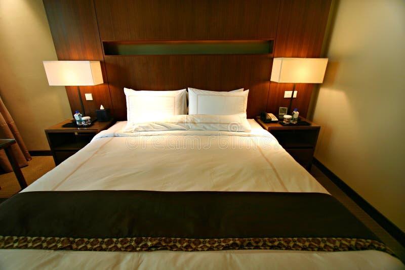 Doppeltes Bett des Hotelschlafzimmers lizenzfreie stockbilder